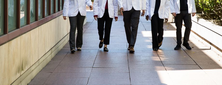 students in white coats, walking