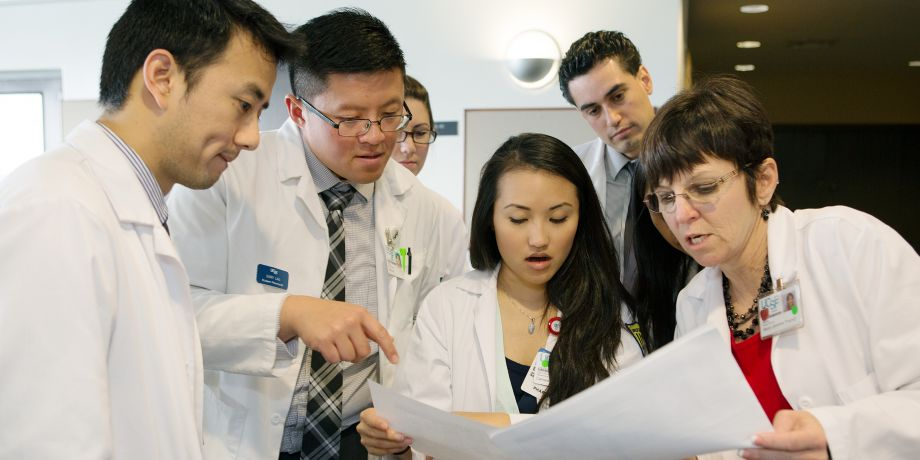 student pharmacists review a list of medications with a resident and faculty member