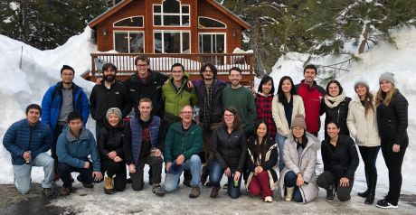 group in front of snow-covered house