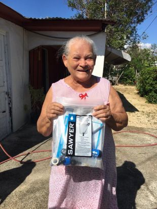 Puerto Rico resident holds a water filter and a sign saying Thank You UCSF.