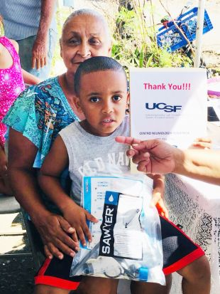 Puerto Rico residents hold a water filter and a sign saying Thank You UCSF.